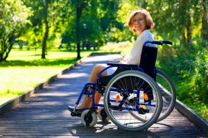 happy young adult woman on wheelchair in the park